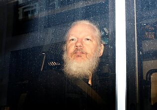 Julianas Assange`as policijos furgone.