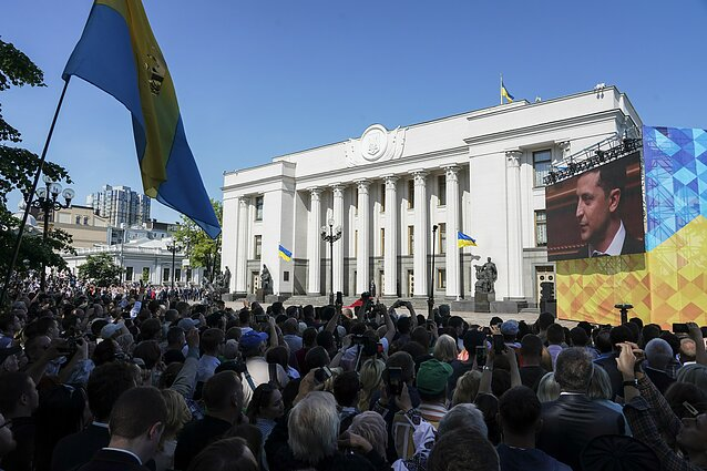 People gather in front of Verkhovna Rada, the Ukrainian parliament, during the inauguration ceremony of new Ukrainian President Volodymyr Zelenskiy, right on the screen, in Kiev, Ukraine, Monday, May 20, 2019.