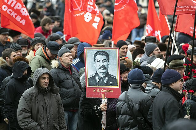 Communist party supporters carry red flags and portraits of Josef Stalin as they line up to place flowers at his grave to mark the 66th anniversary of his death in Moscow, March 5, 2019