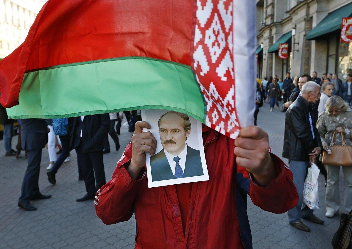 Baltarusijos prezidento Aliaksandro Lukašenkos rėmėjas laiko jo portretą ir mojuoja valstybine šalies vėliava Minsko centre 2015 m. rugsėjo 10 dieną