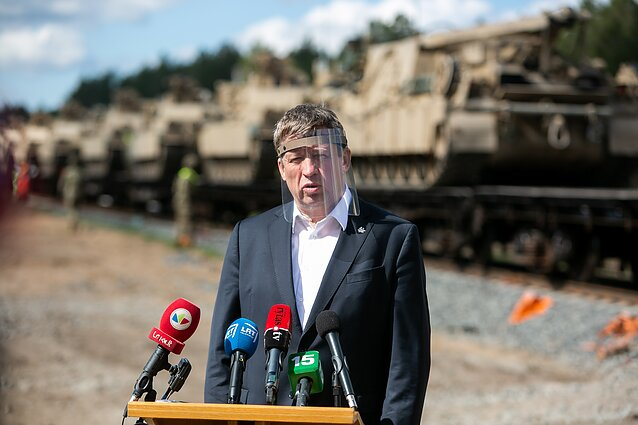 Lithuanian Defence Minister Raimundas karoblis in front of US tanks.